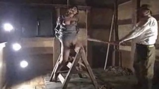 三角木馬に縛りつけられた女囚を激しく竹刀で叩く